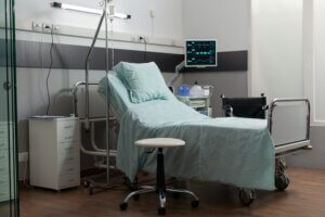Empty bed in hospital room with medical equipment